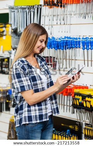 Female customer scanning product's barcode through mobilephone in hardware store - stock photo