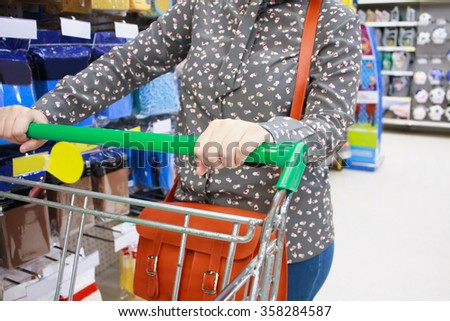 Female customer shopping at supermarket with shopping cart