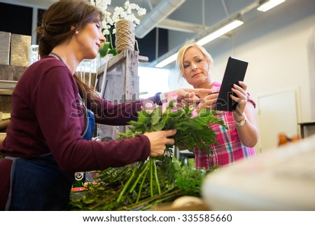 Female customer showing something on digital tablet to florist in flower shop - stock photo