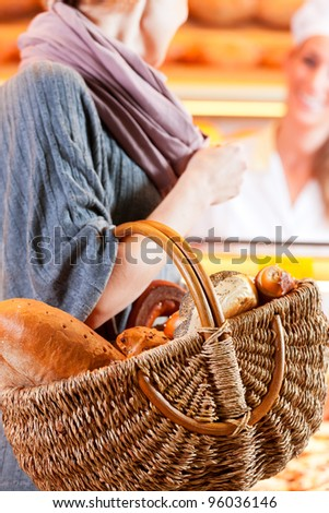 Female customer standing with breadbasket and fresh bread and rolls in bakery - stock photo