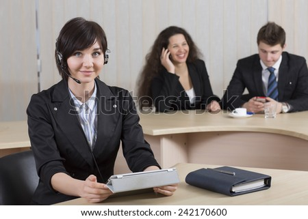 Female customer support manager. Portrait of smiling cheerful customer support phone operator in headset with her co-workers on the background - stock photo