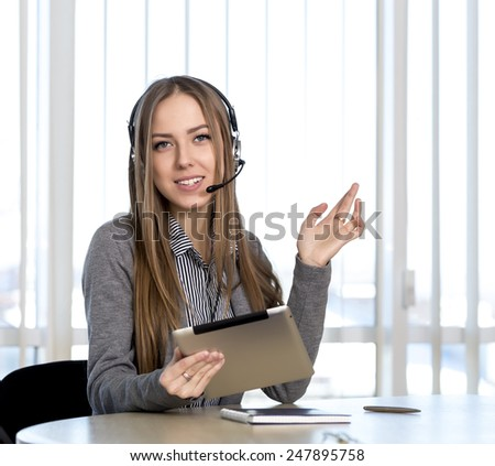 Female customer support officer looking to the camera. Portrait of smiling cheerful customer support phone operator in headset talking to customer - stock photo