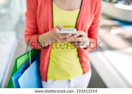 Female customer with cellular phone and shopping bags in the mall - stock photo