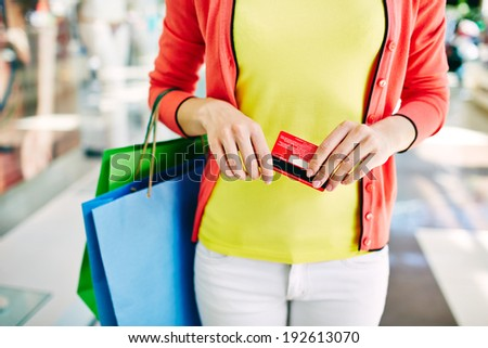 Female customer with plastic card and shopping bags in the mall - stock photo