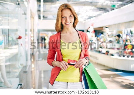 Female customer with plastic card and shopping bags looking at camera in the mall - stock photo