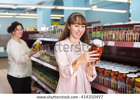 Female customers looking at jars with pickles in food store