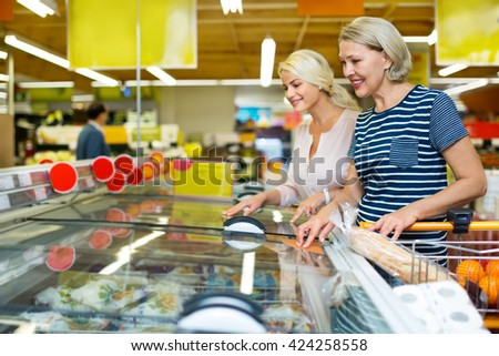 Female customers standing near display with a frozen food at a supermarket  - stock photo
