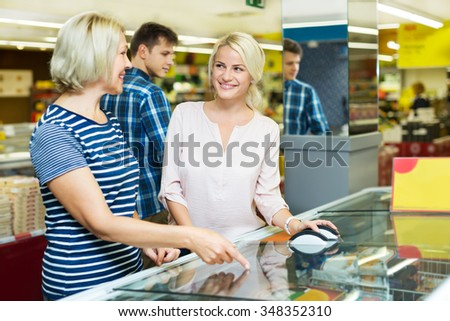 Female customers standing near display with a frozen food at the supermarket  - stock photo