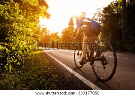 Female cyclist cycling am The path in the woods and mountains - stock photo