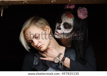 Female daemon with victim in hands. Face painting art.