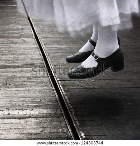 Female dancer in jumping position on theater stage - stock photo