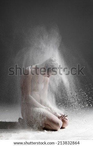 female dancer posing on studio background and flour explosion - stock photo