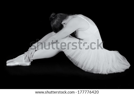 Female dancer sit on floor looking sad in artistic conversion black and white - stock photo