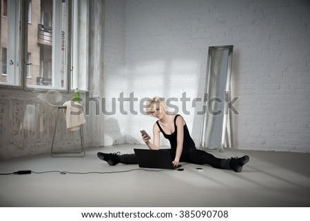 Female dancer sitting on floor using laptop computer and mobilephone. - stock photo
