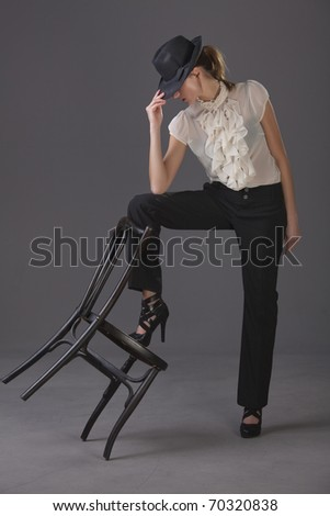 female dancer with hat and chair over grey background - stock photo