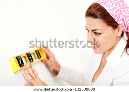 Female decorator holding a level instrument and smiling - stock photo