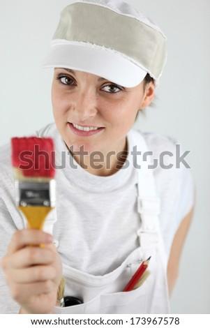 Female decorator holding paint brush - stock photo