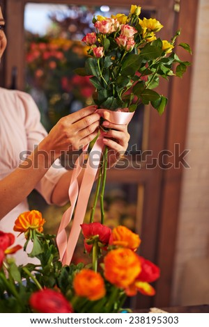 Female decorator tying rose bunch up with silk ribbon