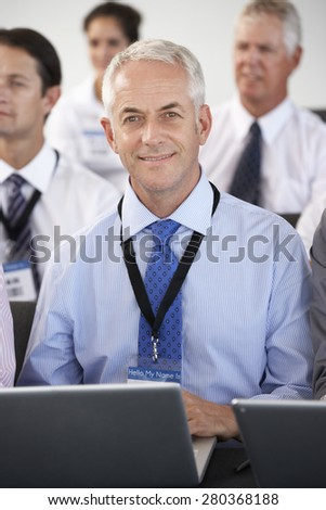 Female Delegate Listening To Presentation At Conference Making Notes On Laptop - stock photo