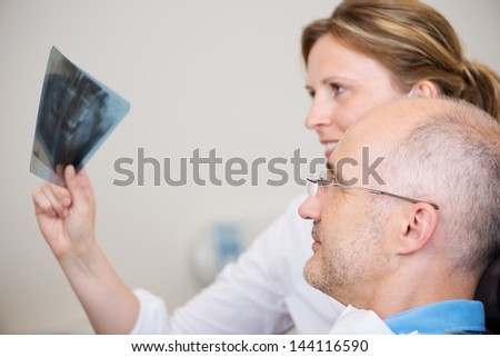 Female dentist and patient examining Xray in clinic - stock photo