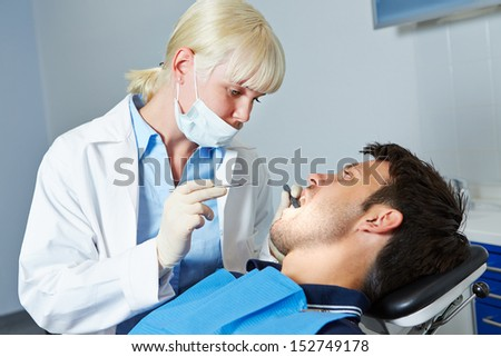 Female dentist examining denture of patient with toothache