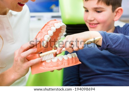 Female dentist explaining boy cleaning tooth with toothbrush on model  - stock photo