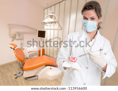 Female dentist holding a denture and a syringe explaining the treatment