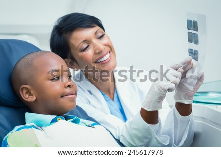 Female dentist showing young boy his mouth x-ray in the dentists chair - stock photo