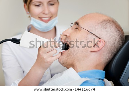Female dentist with dental camera examining patient's teeth at clinic - stock photo