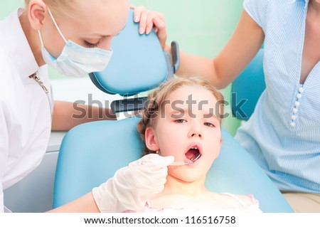 female dentists examines a child, my mother was sitting beside him and soothes baby