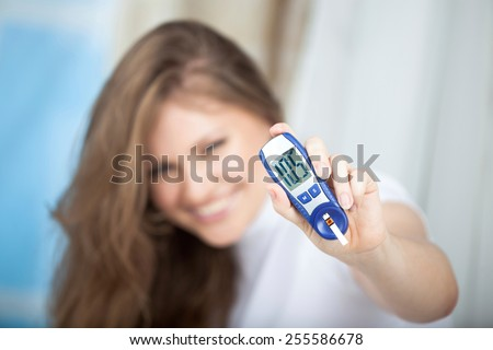 Female Diabetic Showing a Glucose Level Finger Blood Test with Good Result . Selective Focus is in the Hand - stock photo