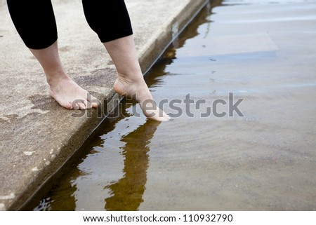 Female dipping her toes into the water. - stock photo