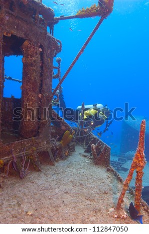 Female diver exploring the superstructure of the gunship, The Tibbetts, off Cayman Brac. - stock photo