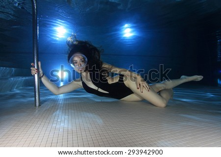 Female diver with one-piece swimsuit and dive mask posing underwater in the pool - stock photo