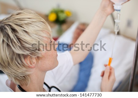 Female doctor adjusting infusion bottle with patient lying on bed in hospital - stock photo