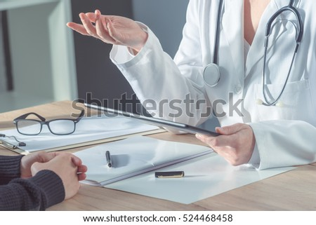 Female doctor advising patient in hospital office during regular medical exam, healthcare and prevention concept.