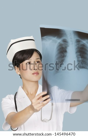 Female doctor analyzing x-ray report over light blue background