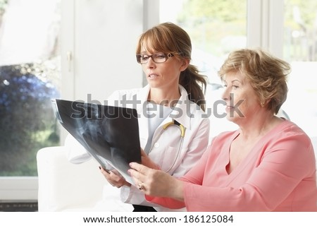 Female doctor analyzing x-ray with senior patient at small clinic. - stock photo