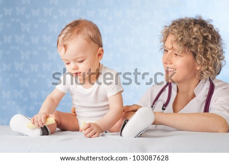 Female doctor and baby patient. - stock photo