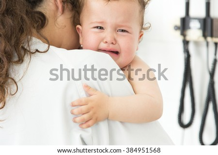 Female doctor attending to a baby crying in the query - stock photo