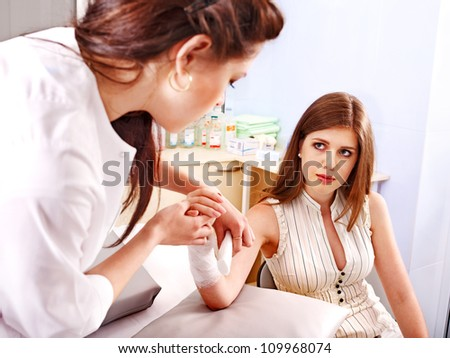 Female doctor bandaging patient in hospital. - stock photo