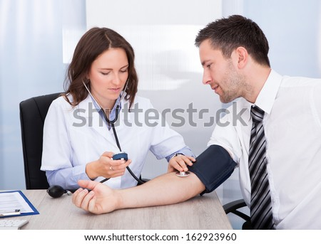 Female Doctor Checking Blood Pressure Of Young Businessman - stock photo