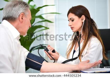 Female doctor checking his patient's blood pressure - stock photo