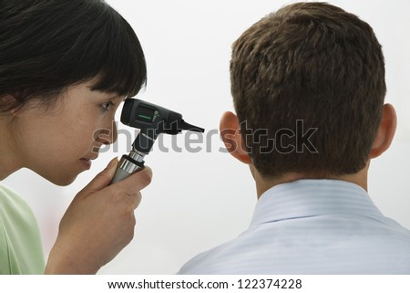 Female doctor checking patient ear with otoscope - stock photo