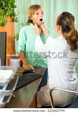 Female doctor checking thyroid of young patient at the table in clinic  - stock photo