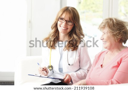 Female doctor consulting with senior patient at private clinic.  - stock photo