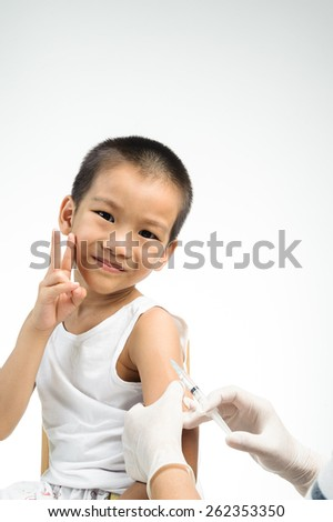 Female doctor doing injection to little boy that not fear - stock photo