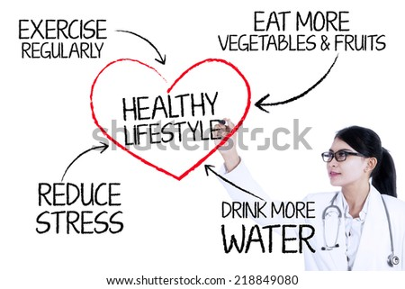 Female doctor drawing healthy lifestyle concept with marker on glass wall - stock photo