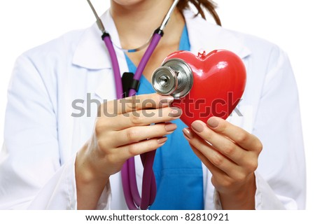 Female doctor examining a red heart with a stethoscope against white background - stock photo