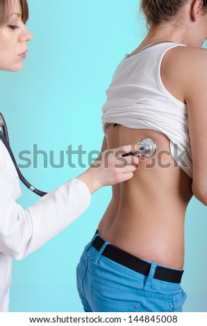 Female doctor examining a young woman - stock photo